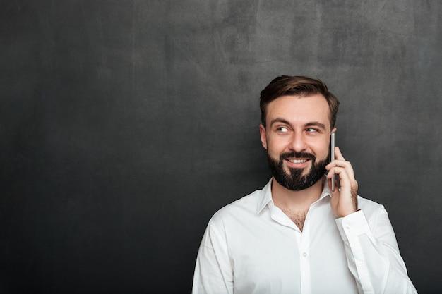 Uomo felice che parla sul telefono cellulare che ha conversazione piacevole che guarda da parte sopra lo spazio della copia della grafite