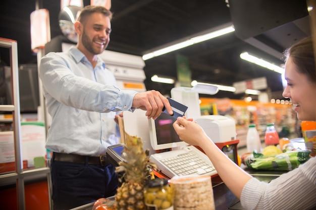 Uomo felice che passa la carta di credito al cassiere in supermercato