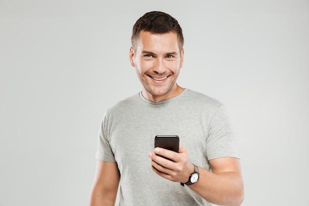 Uomo felice che per mezzo della chiacchierata del telefono cellulare.