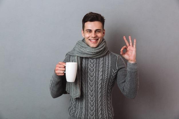 Uomo felice che porta sciarpa calda che mostra gesto giusto.
