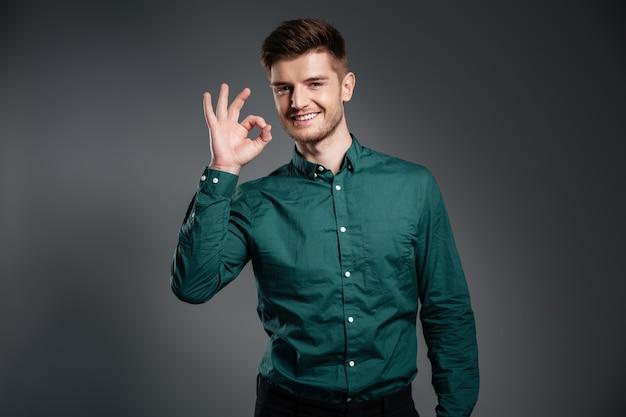 Uomo felice che posa sopra il gray che mostra gesto giusto.