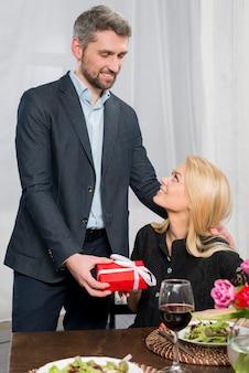 Uomo felice che presenta il contenitore di regalo alla donna alla tavola