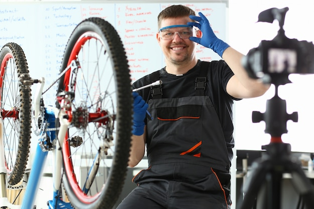 Uomo felice che registra gli occhiali di protezione e che si siede vicino alla bicicletta