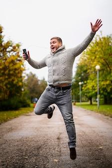Uomo felice che salta su nel parco