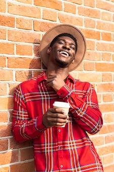 Uomo felice che si appoggia su un muro di mattoni