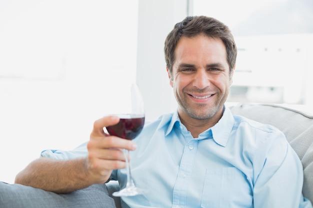 Uomo felice che si distende sul divano con un bicchiere di vino rosso
