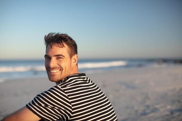 Uomo felice che si distende sulla spiaggia