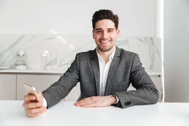 Uomo felice che si siede dalla tavola con lo smartphone a casa