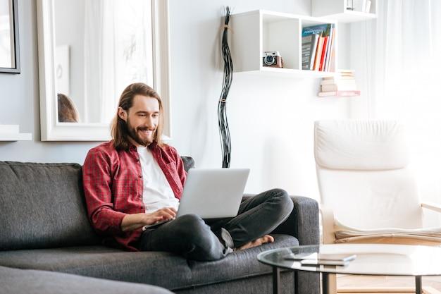 Uomo felice che si siede sul sofà e che per mezzo del computer portatile a casa