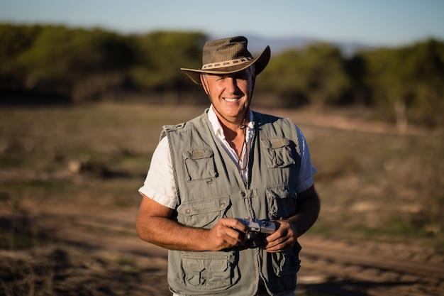Uomo felice che sta con la macchina fotografica durante la vacanza di safari