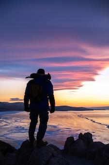 Uomo felice che sta sulla scogliera e che esamina vista del paesaggio