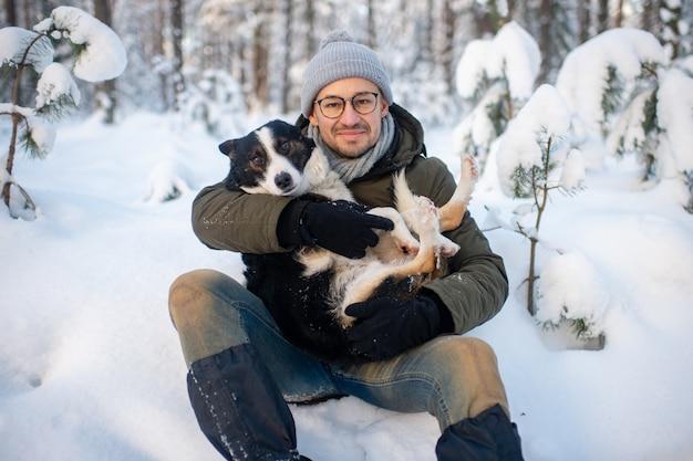Uomo felice che tiene cane adorabile in sue mani in foresta nevosa.