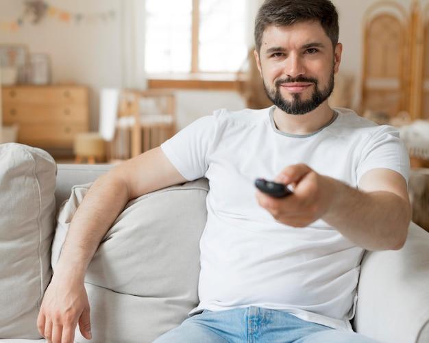 Uomo felice che tiene un telecomando e seduto sul divano