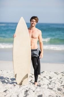 Uomo felice che tiene una tavola da surf sulla spiaggia