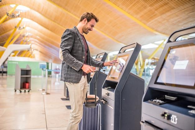 Uomo felice che utilizza la macchina di registrazione all'aeroporto che ottiene la carta d'imbarco.