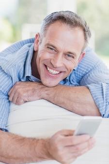 Uomo felice che utilizza smartphone nel salone