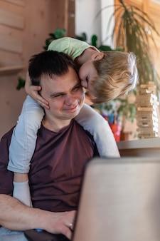 Uomo felice con i bambini che utilizzano computer portatile e trasduttore auricolare durante il suo lavoro domestico, vita nella quarantena