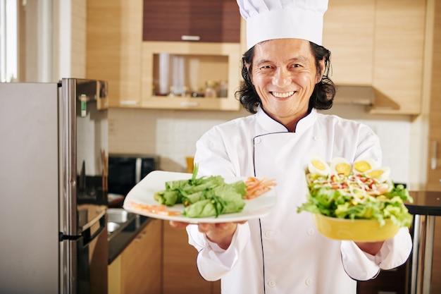 Uomo felice con i piatti che ha cucinato