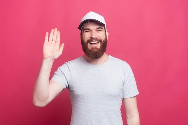 Uomo felice con il cappello da portare della barba e dire ciao