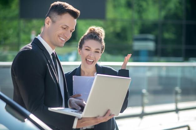 Uomo felice con il computer portatile e la donna con i documenti