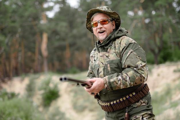 Uomo felice con il fucile da caccia che cerca attività all'aperto.