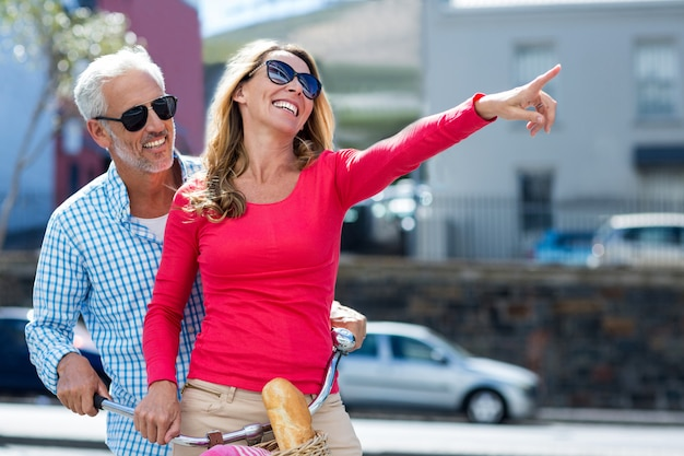 Uomo felice con la donna che indica alla via della città