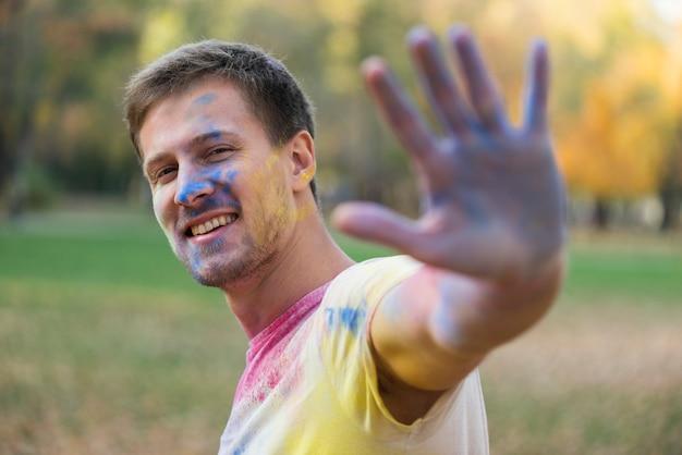 Uomo felice con la mano e la faccia colorate a holi