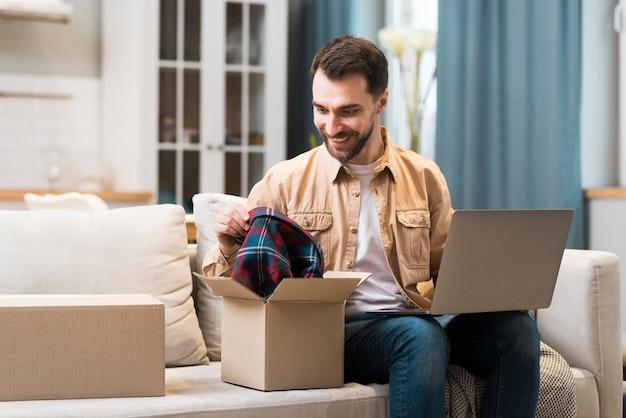 Uomo felice con la sua scatola della spesa online che è arrivata