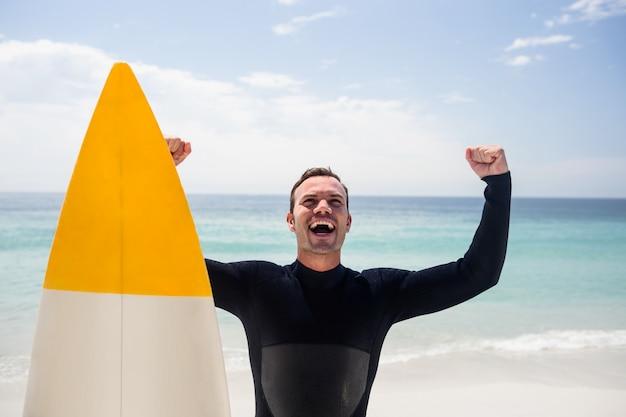 Uomo felice con la tavola da surf che sta sulla spiaggia