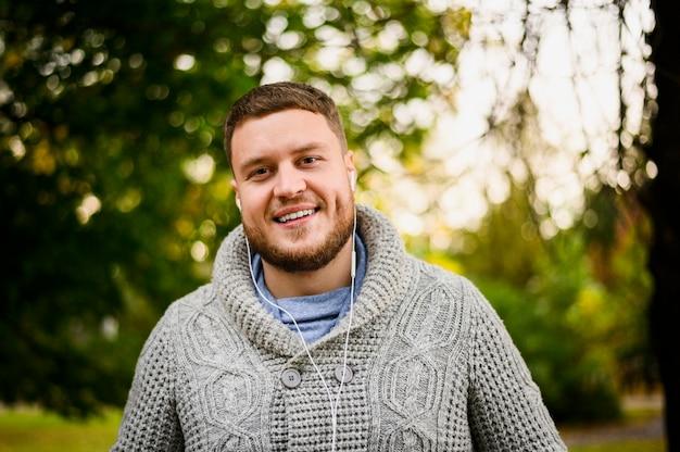 Uomo felice con le cuffie che sorride alla macchina fotografica