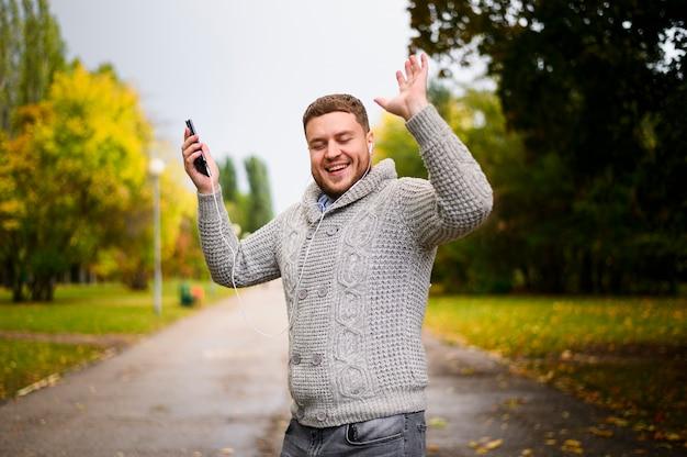 Uomo felice con le sue mani in su nel parco