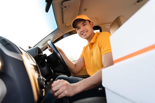 Uomo felice consegna con scatola di cartone pacchi in auto. consegna del corriere sorridente
