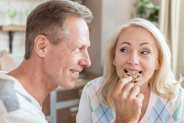 Uomo felice del colpo medio che alimenta il suo partner