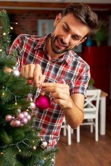 Uomo felice del colpo medio che decora l'albero di natale