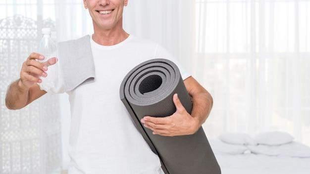 Uomo felice del primo piano con la stuoia di yoga e dell'acqua
