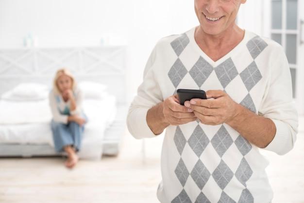 Uomo felice del primo piano con lo smartphone nella camera da letto