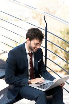 Uomo felice dell'angolo alto sulle scale con il computer portatile