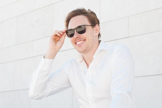 Uomo felice di affari che regola gli occhiali da sole all'aperto