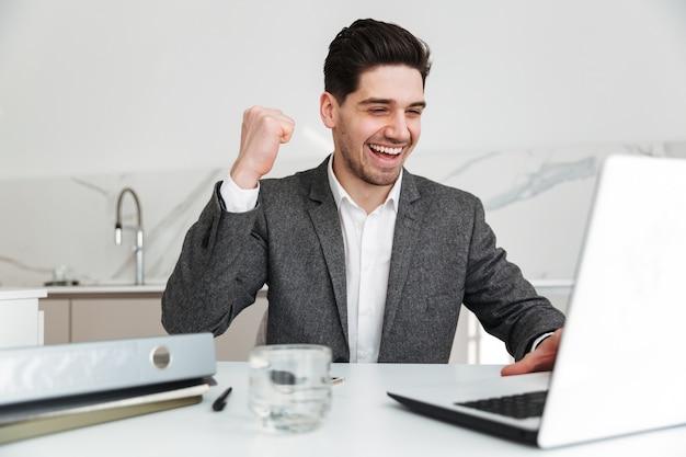 Uomo felice di affari che si siede dalla tabella a casa