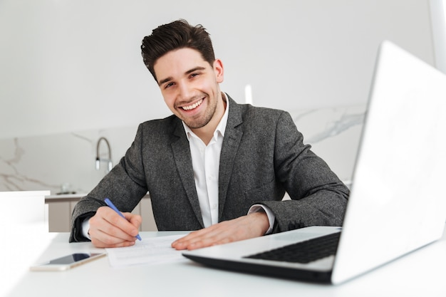 Uomo felice di affari che si siede dalla tabella con il computer portatile