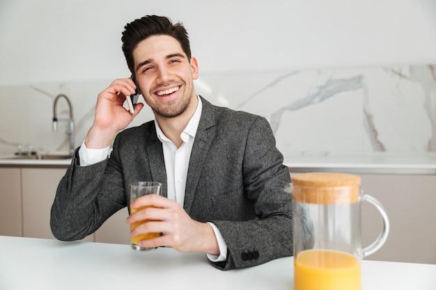 Uomo felice di affari che si siede dalla tabella e che giudica di vetro