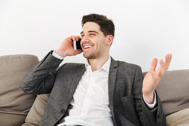 Uomo felice di affari che si siede sul sofà a casa