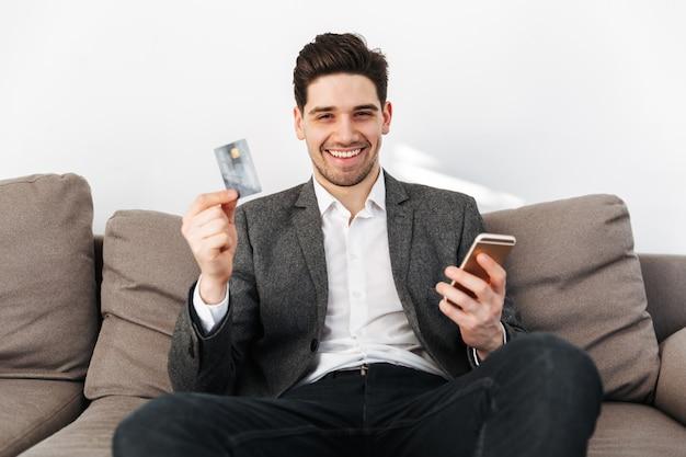 Uomo felice di affari che si siede sul sofà con lo smartphone a casa