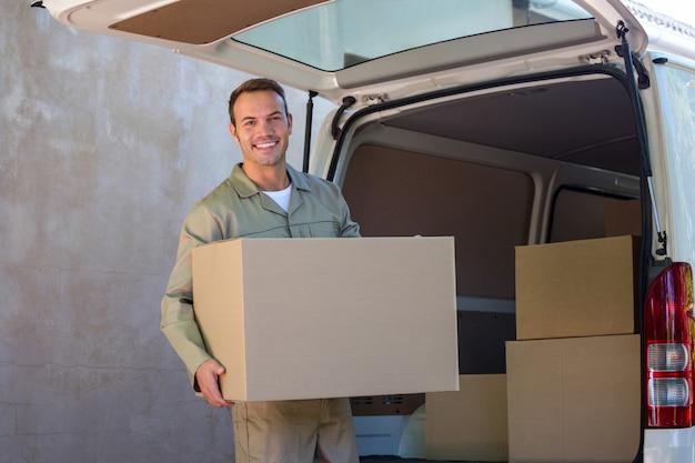 Uomo felice di consegna che trasporta una scatola di cartone