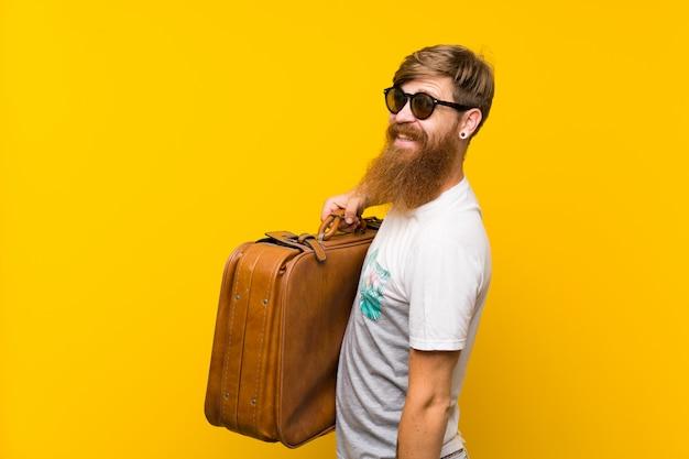 Uomo felice di redhead con la barba lunga che tiene una cartella dell'annata