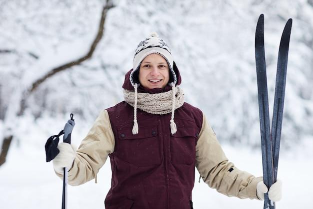 Uomo felice di sciare nella foresta