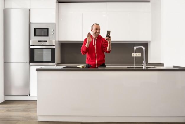 Uomo felice divertendosi e parlando della video chiamata online nella cucina a casa