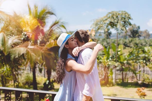 Uomo felice e donna che abbracciano sul terrazzo o sul balcone con le giovani coppie del bello paesaggio tropicale dentro