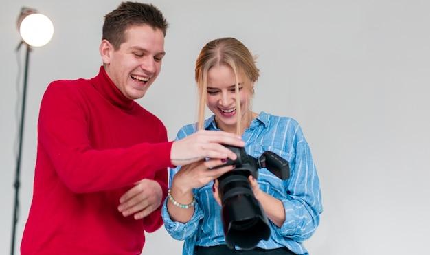 Uomo felice e donna che guardano attraverso le foto in studio