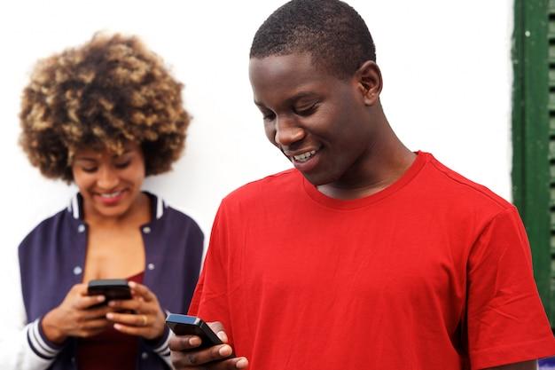 Uomo felice e donna che utilizzano i telefoni cellulari all'aperto